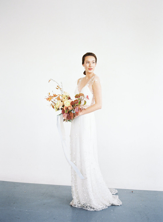 The bride was wearing a chic gown with illusion straps, a cropped waist and appliques