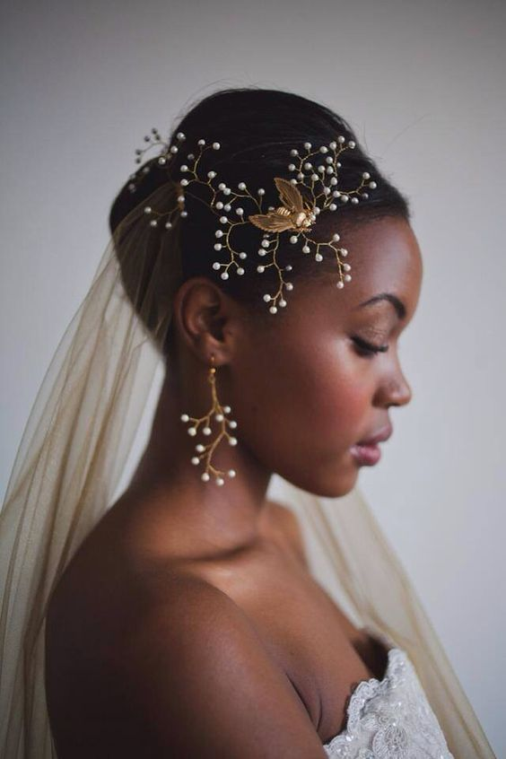 a bride wearing a gold veil and matching accessories with pearls and gold