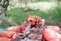 08 a colorful picnic setting with coral and red tones, a low vintage table and bright textiles
