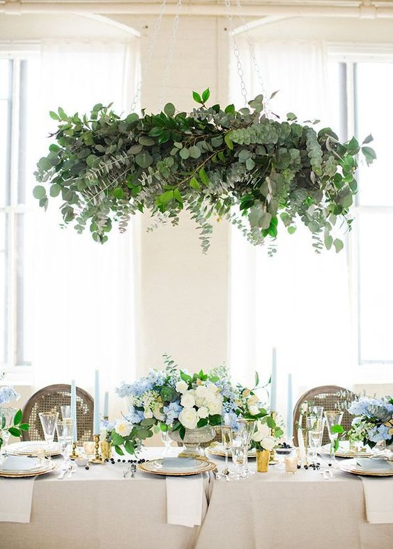 a dramatical leafy chandelier draped with eucalyptus and camellia foliage is a showpiece