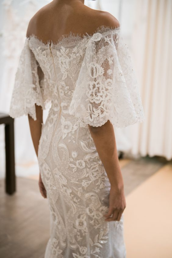 a refined lace sheath off the shoulder wedding dress with bell sleeves by Marchesa