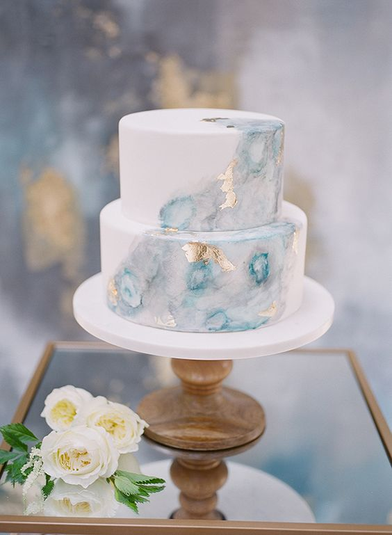 a watercolor marble light blue wedding cake decorated with gold leaf is a very chic and trendy idea - three trends in one