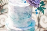 08 a watercolor wedding cake in the shades of lilac and turquoise with a large purple floral and blue berries on top