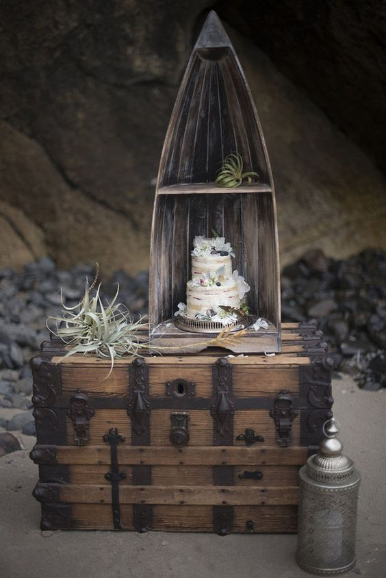 a wedding cake displayed a part of a boat, on a large chest with air plants