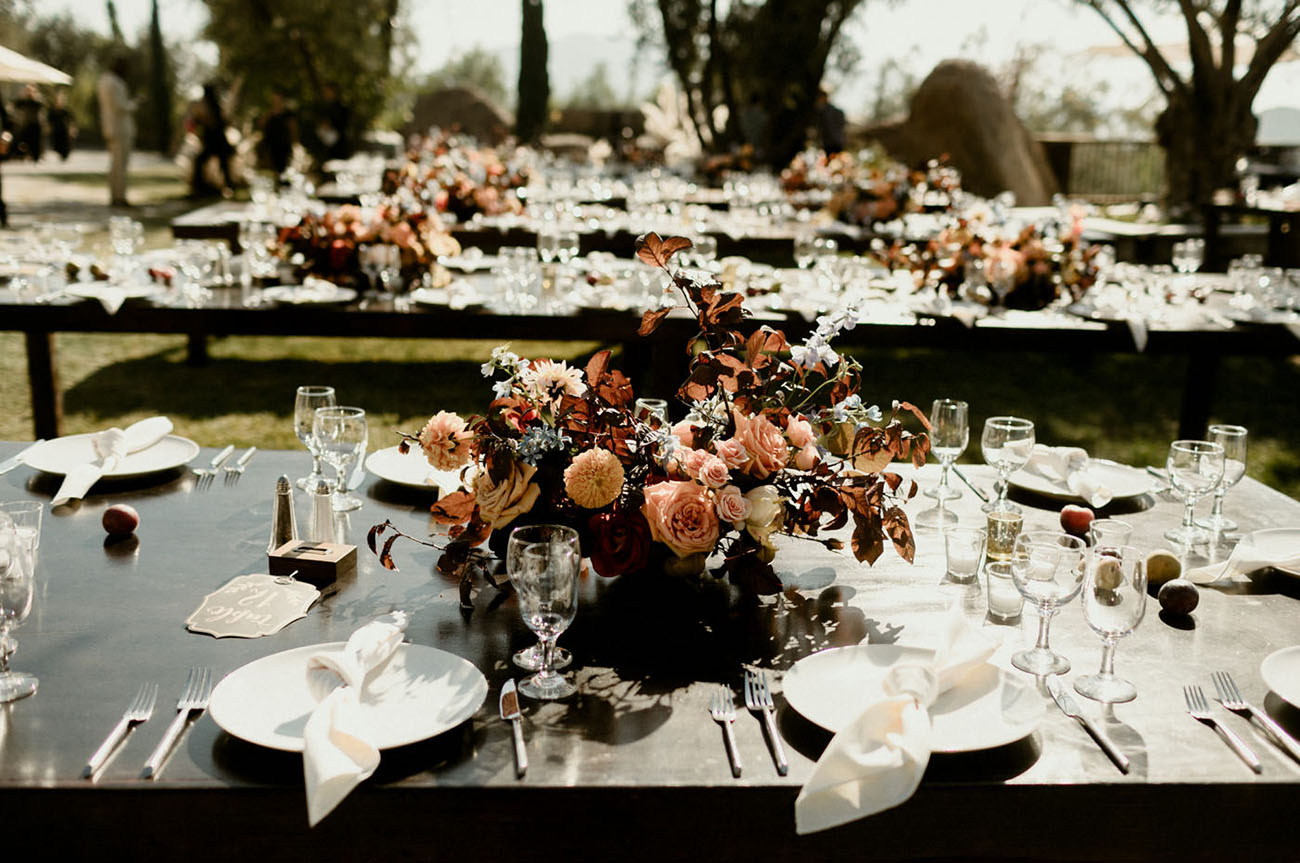 the table settings were done with lush florals, bare tables and some fruit   persimmons and peaches for a southern feel