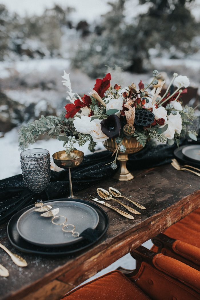 The wedding table setting was done with black linens, moody florals and elegant gold touches