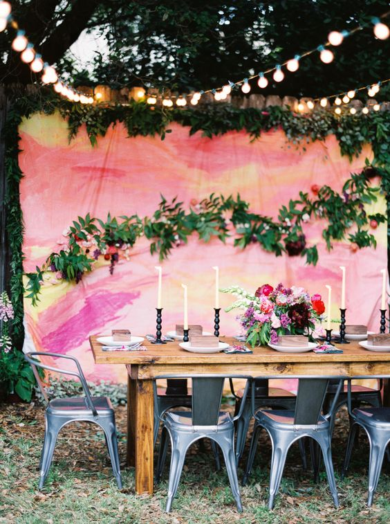 a bold watercolor backdrop in pink, coral and yellow plus natural greenery and blooms