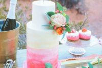 09 a coral and pink watercolor wedding cake is topped with a flirty gold cake topper