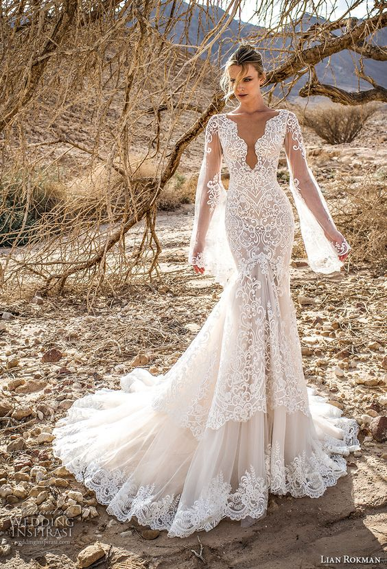 a gorgeous mermaid wedding dress with a plunging neckline, a train, bell sleeves and embroidery