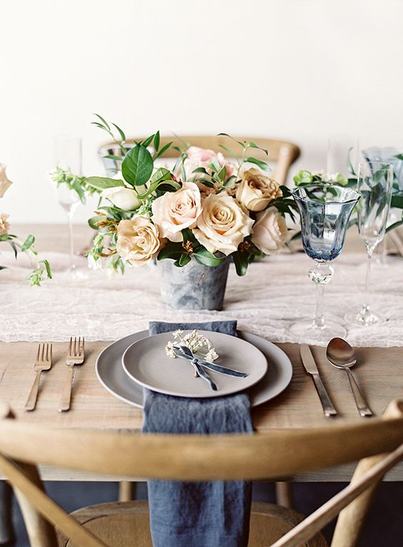 a moody spring wedding centerpiece with neutral blooms and some greenery