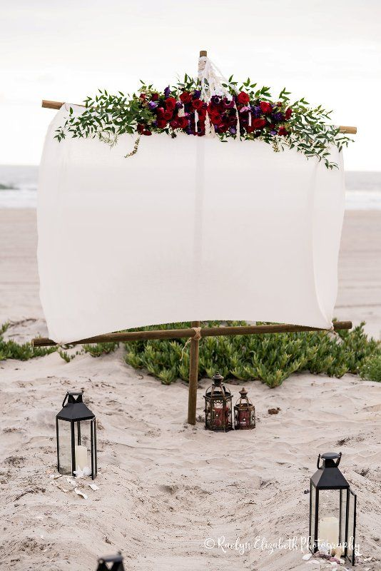a wedding backdrop of sail cloth topped with bold florals and greenery plus candle lanterns