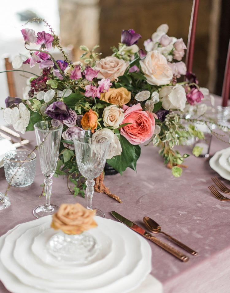 the tablescape was done with lush florals, exquisite glasses and cutlery plus a mauve tablecloth