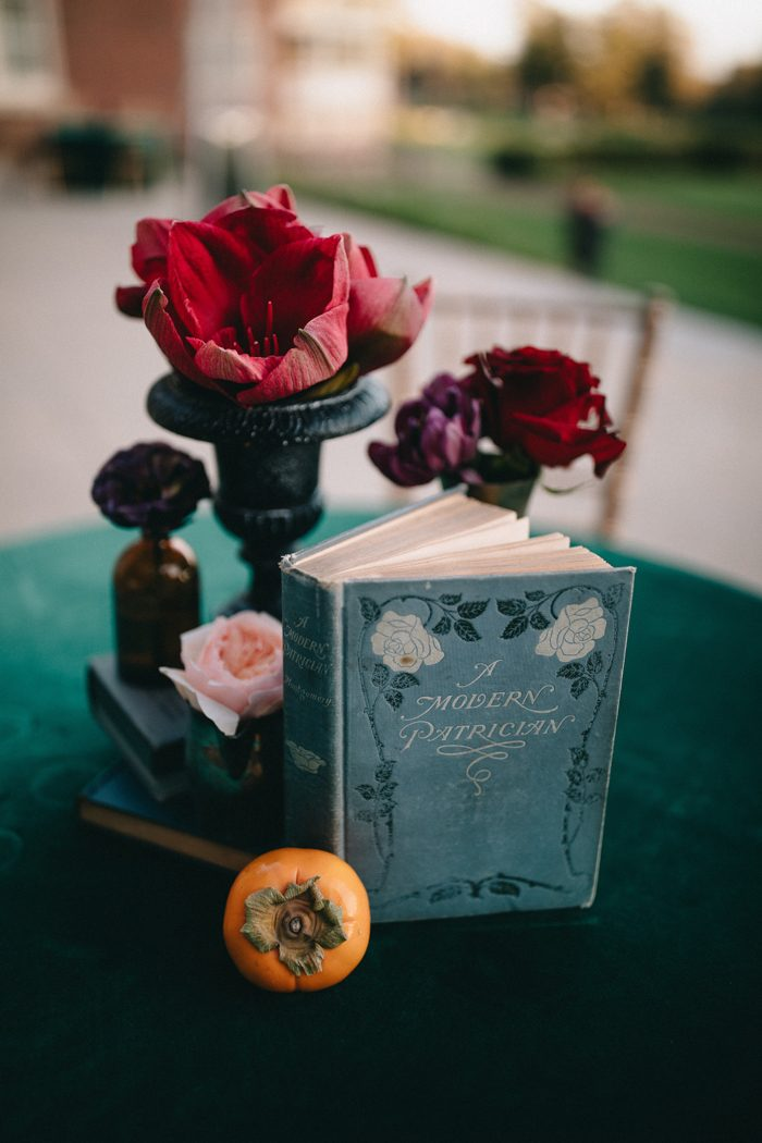 The wedding centerpieces were done with bold florals, vintage books and fruits