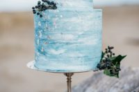 10 a blue watercolor wedding cake with silver flakes and some berries looks refined