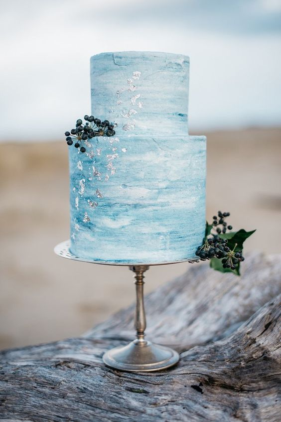a blue watercolor wedding cake with silver flakes and some berries looks refined