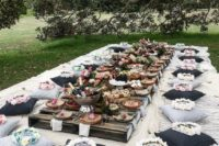 10 a gorgeous boho picnic setting with pallet tables, black and grey pillows and tables styled with fruit and food instead of blooms