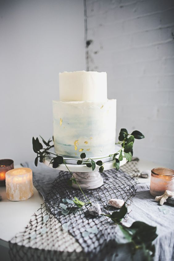 a light blue watercolor wedding cake with a rough edge, gold flakes and some greenery around