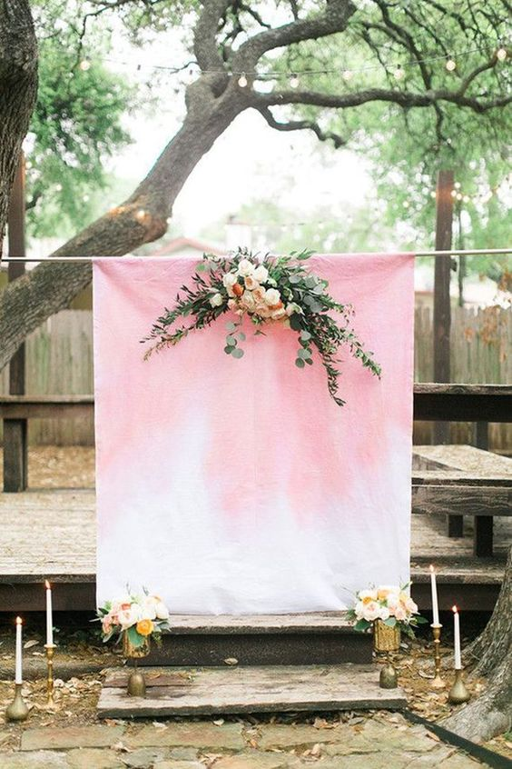 a light pink watercolor ombre wedding backdrop decorated with greenery and fresh blooms