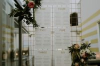 10 a metal grid with seating charts and fresh greenery and blooms
