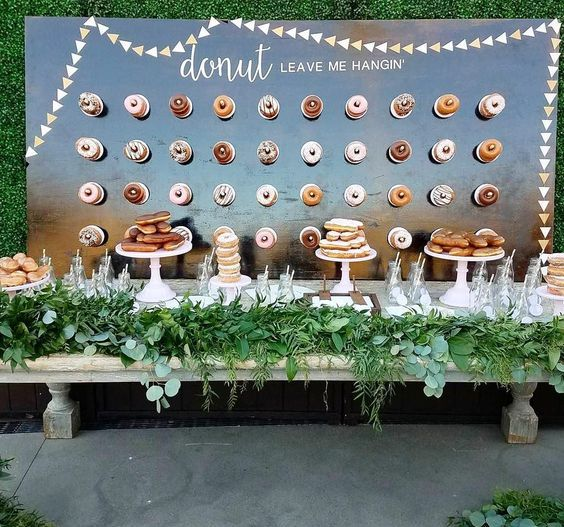 a polished wall with stenciled letters as a backdrop for the dessert bar