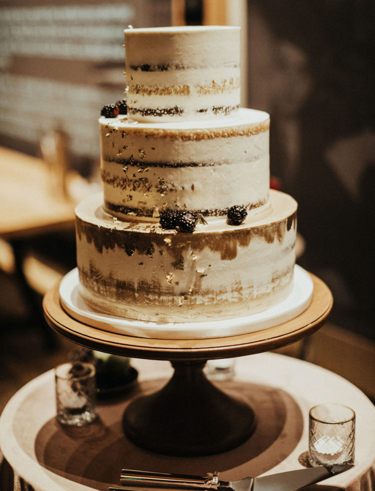 The wedding cake was a naked one with gold leaf and blackberries
