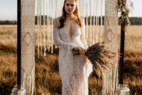 11 a boho lace wedding dress with a cutout on the neckline, long bell sleeves and a train