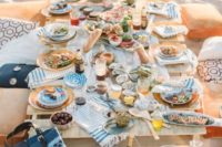 11 a comfy picnic setting with a boho feel and printed touches right on the beach, what can be better