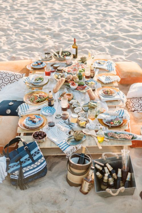a comfy picnic setting with a boho feel and printed touches right on the beach, what can be better