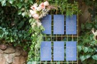 11 a gilded metal grid with navy and gold seating chart sheets and fresh greenery and flowers