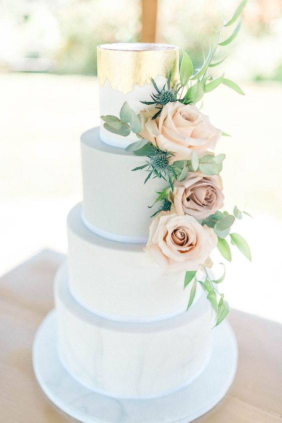 a powder blue wedding cake with gold leaf decor and blush roses and thistles is a very elegant choice