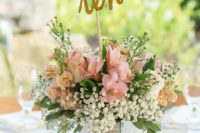 11 a rustic bucket with pink blooms, baby's breath and a calligraphy table number