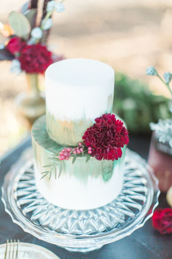 a watercolor green wedding cake with copper touches and a large burgundy bloom with berries