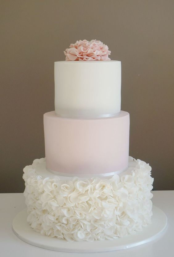 a blush and white wedding cake with ruffles on the white tier and on top