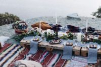 12 a cozy picnic setting by the seaside with pallet tables, printed textiles, simple greenery and blooms and candles