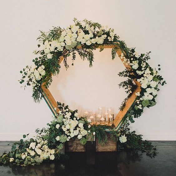 a large hexagon wooden arch with candles, lush white blooms and greenery all over
