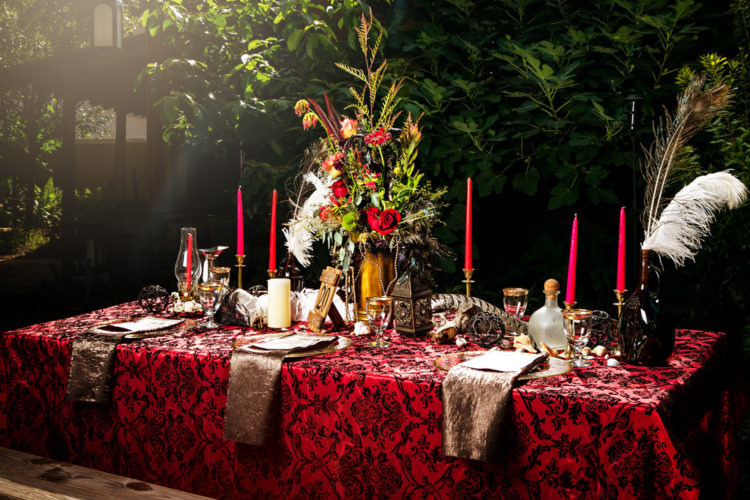 a pirate-inspired wedding tablescape with a printed tablecloth, a lush floral centerpiece, metallic napkins and bold candles