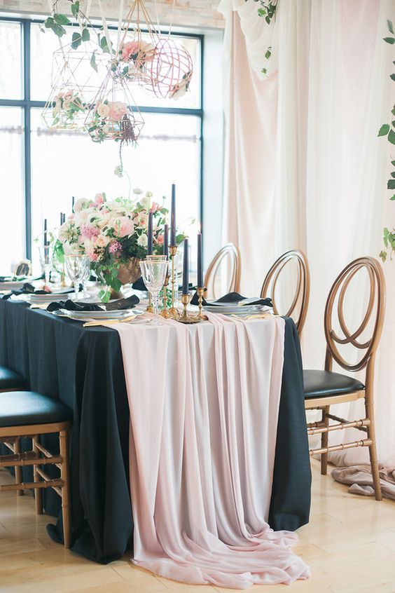 a refined tablescape with a black tablecloth, a pink table runner, black candles and lush florals