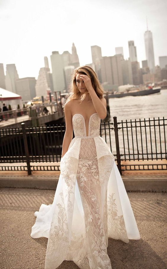 a strapless plunging neckline sheath wedding dress with an overskirt and lace appliques by Berta
