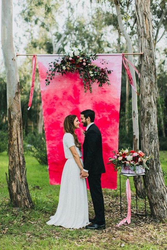 a super bold hot pink and fuchsia watercolor wedding backdrop with lush florals