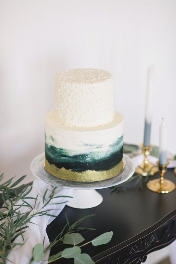 a wedding cake with a textural top tier and a watercolor one in gold, dark green and emerald