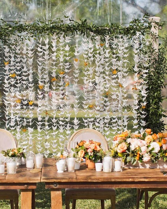 a whimsical wedding backdrop with white and yellow cranes and a greenery garland