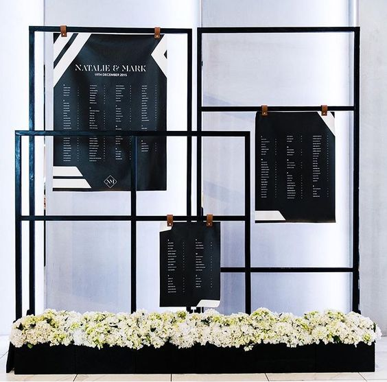 black frames attached to the flower box and geometric seating charts hanging on leather pieces