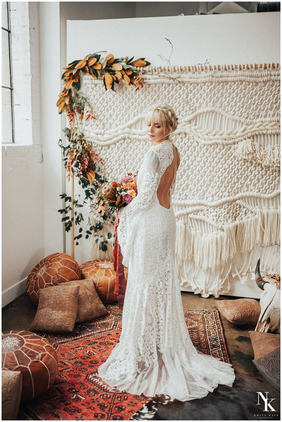 a boho lace wedding gown with a high neckline, a cutout back, bell sleeves