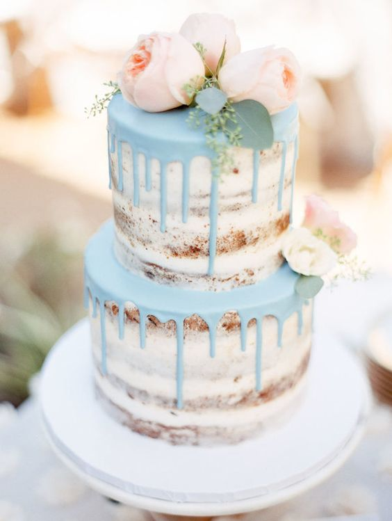 a naked wedding cake with pastel blue drip and some peachy pink blooms
