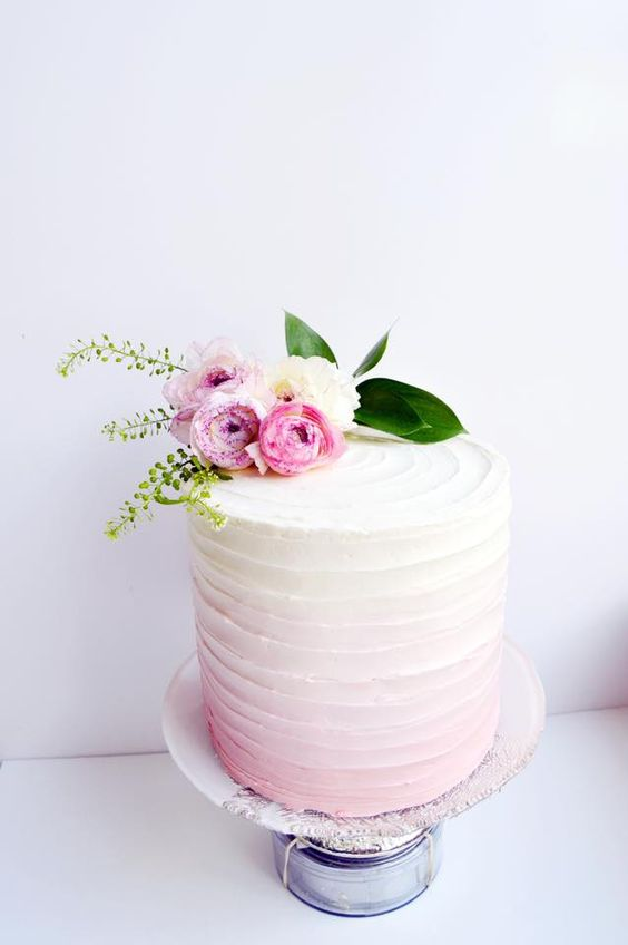 a soft ombre pink wedding cake with a texture and baby roses on top