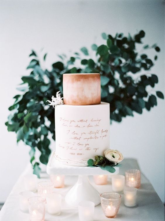a wedding cake with copepr calligraphy and a peachy pink watercolor tier plus blooms for a romantic wedding