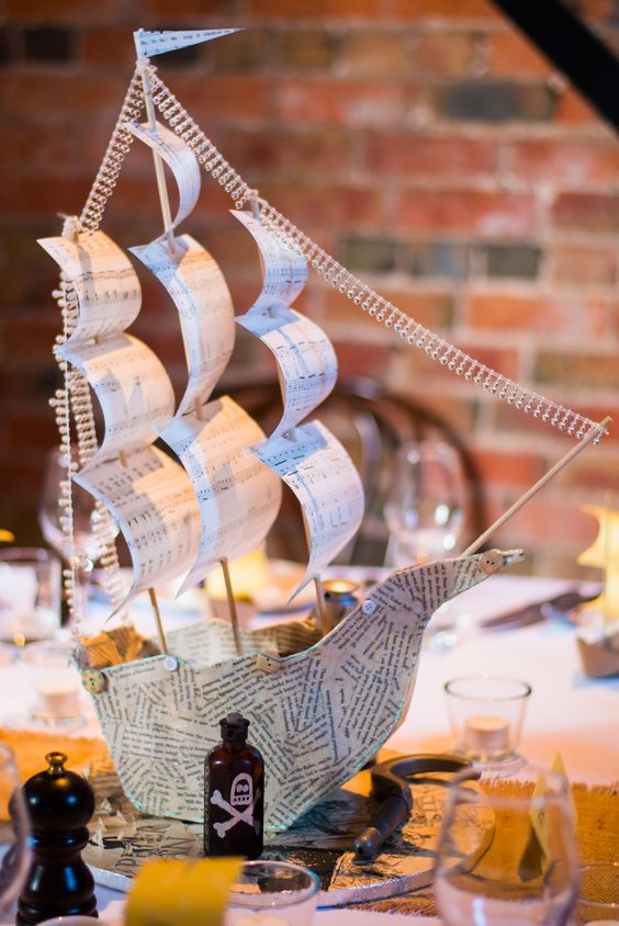 a wedding centerpiece of  paper ship with rhinestones and some poison bottles