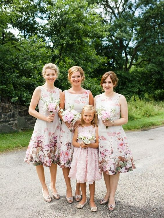 knee bridesmaids' dresses with a bateau neckline and bold floral prints and metallic shoes
