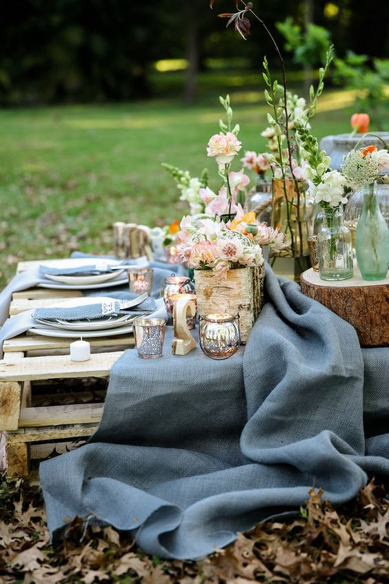 a garden picnic setting with muted tone textiles, pallet tables, lush blooms and some rustic touches