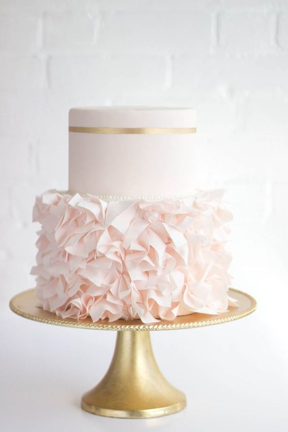 a glam wedding cake with blush ruffled and a gold leaf touch